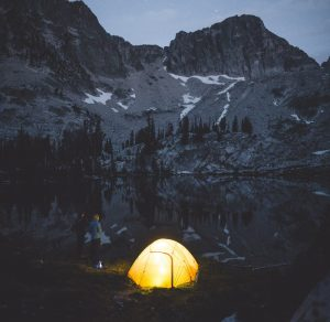 couple-setting-tent-by-mountain-lake-dawn