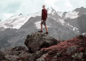 mountain-climber-standing-on-a-rock-snowy-mountain-view